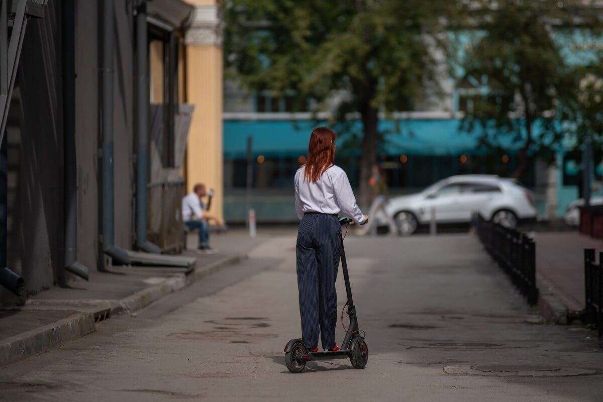 Red hair woman riding e-scooter in the street