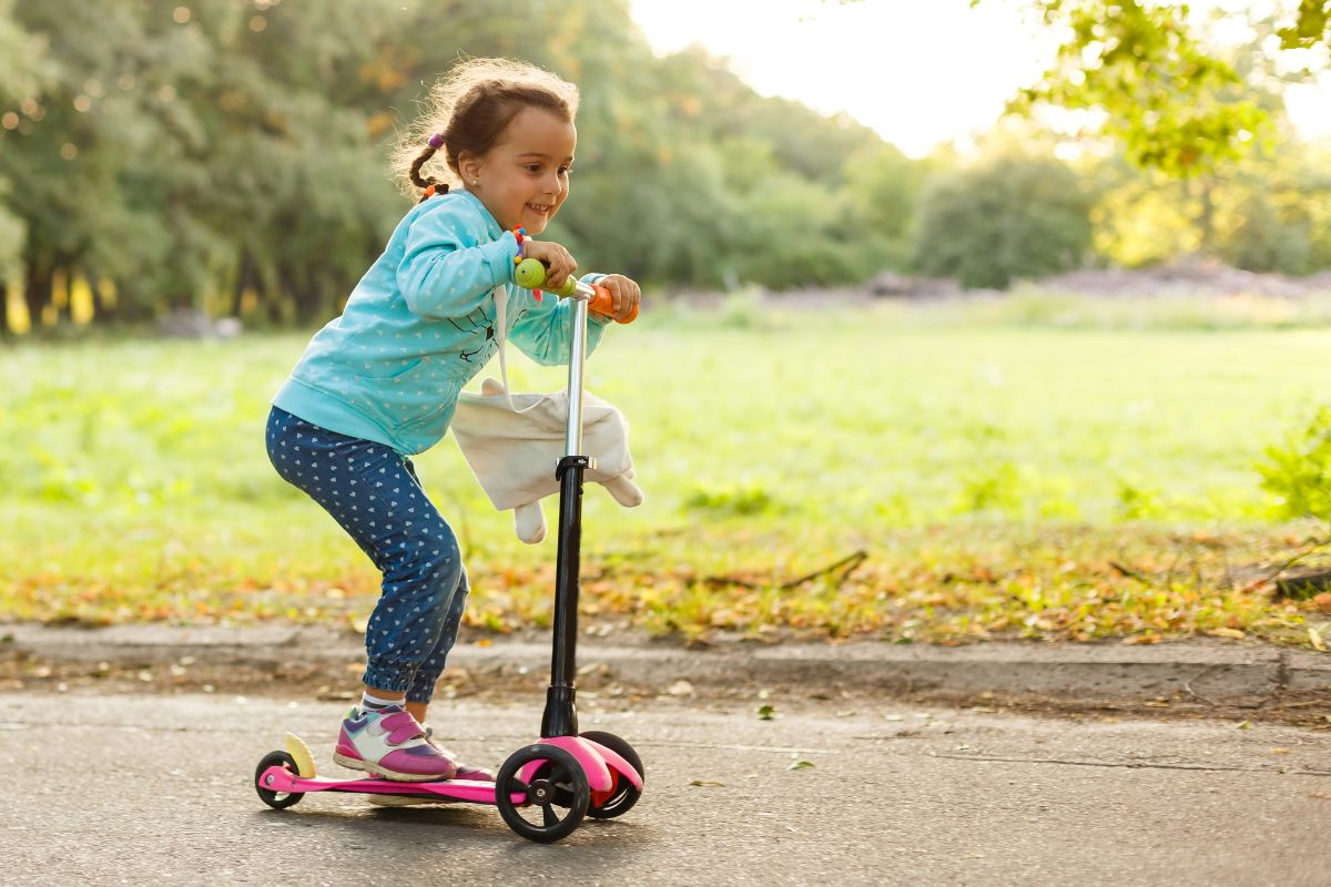 kid riding with her 3-wheeled escooter