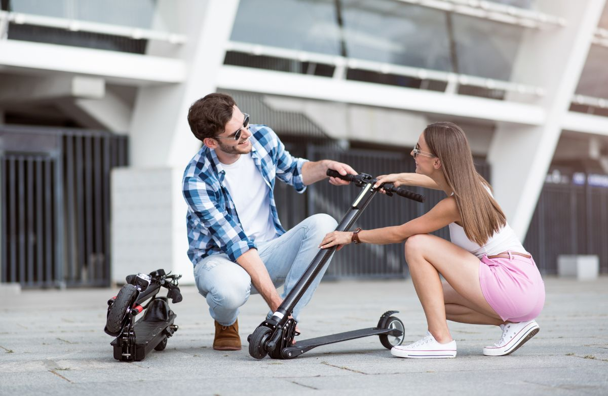Couple unfolding the electric scooter
