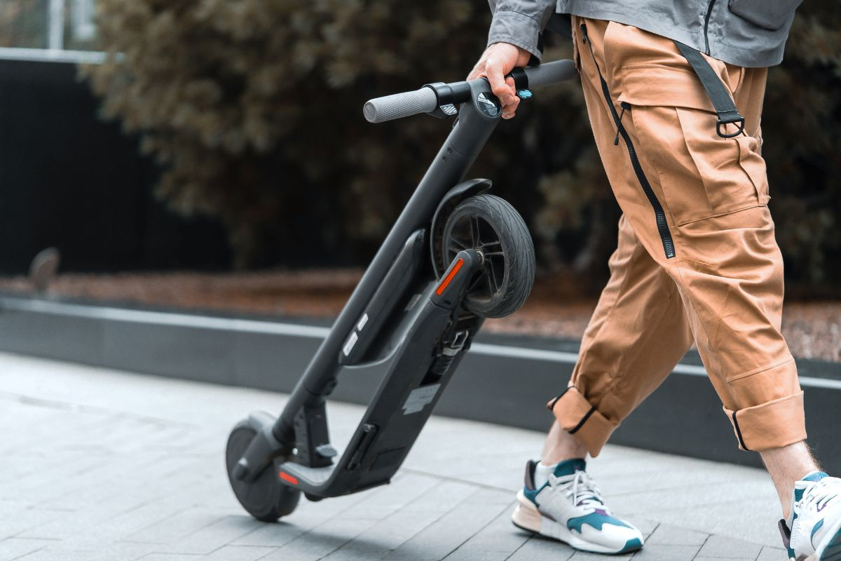 Man with folded electric scooter