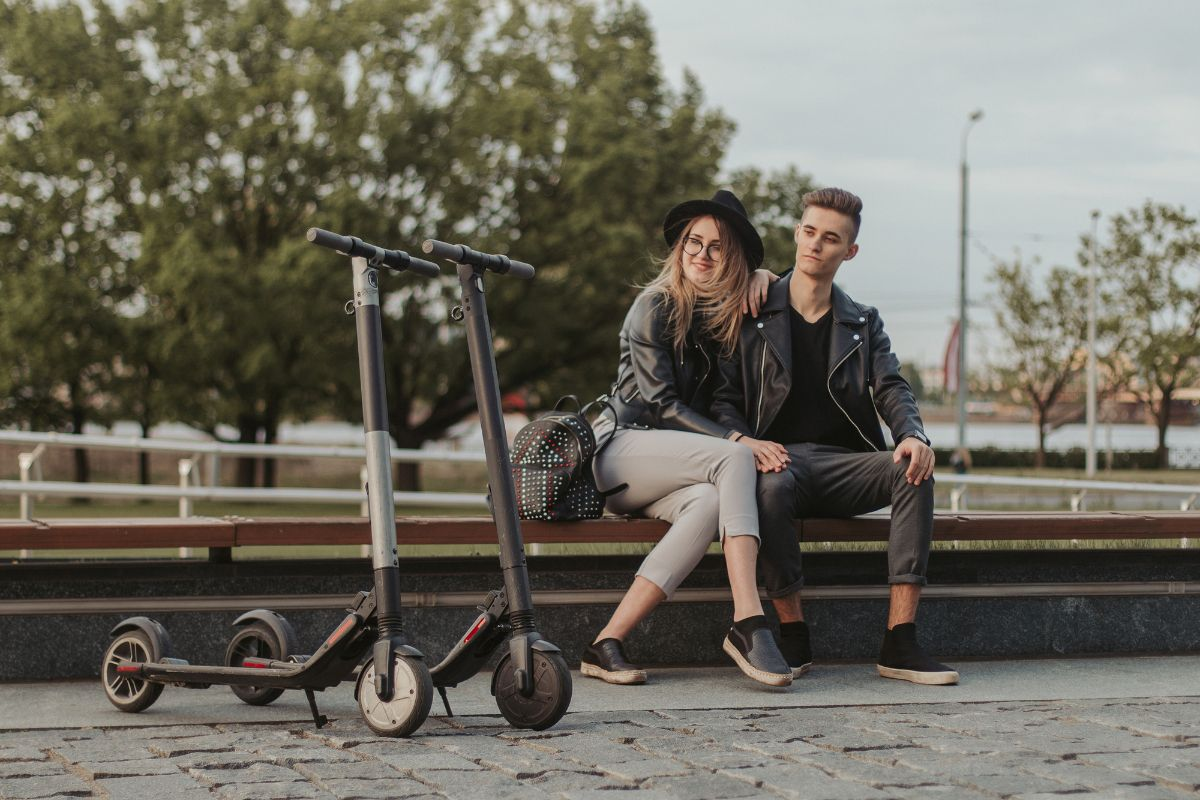 couple with resting with parked electric scooter