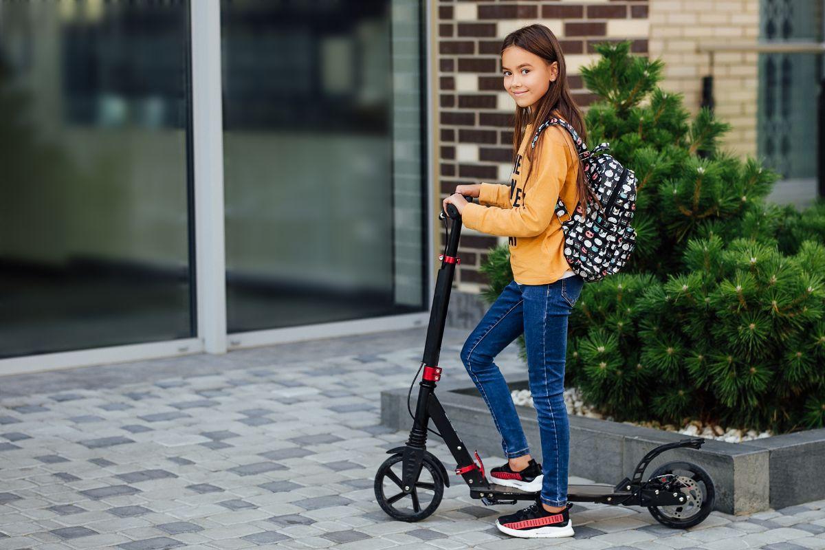 girl on yellow sweatshirt on electric scooter