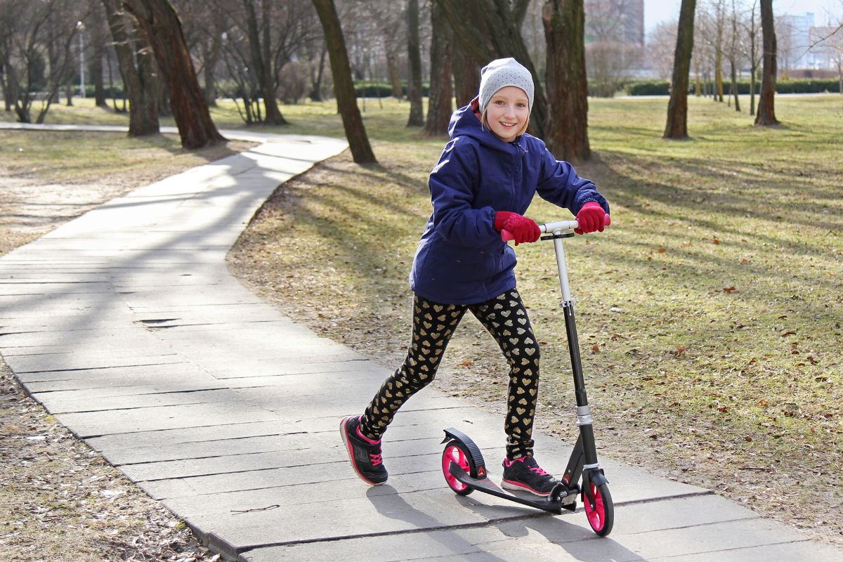 girl with bonnet riding on her scooter