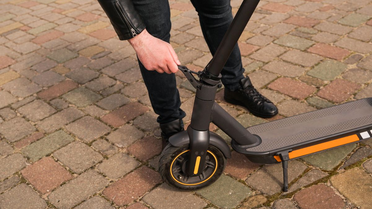 man about to fold electric scooter