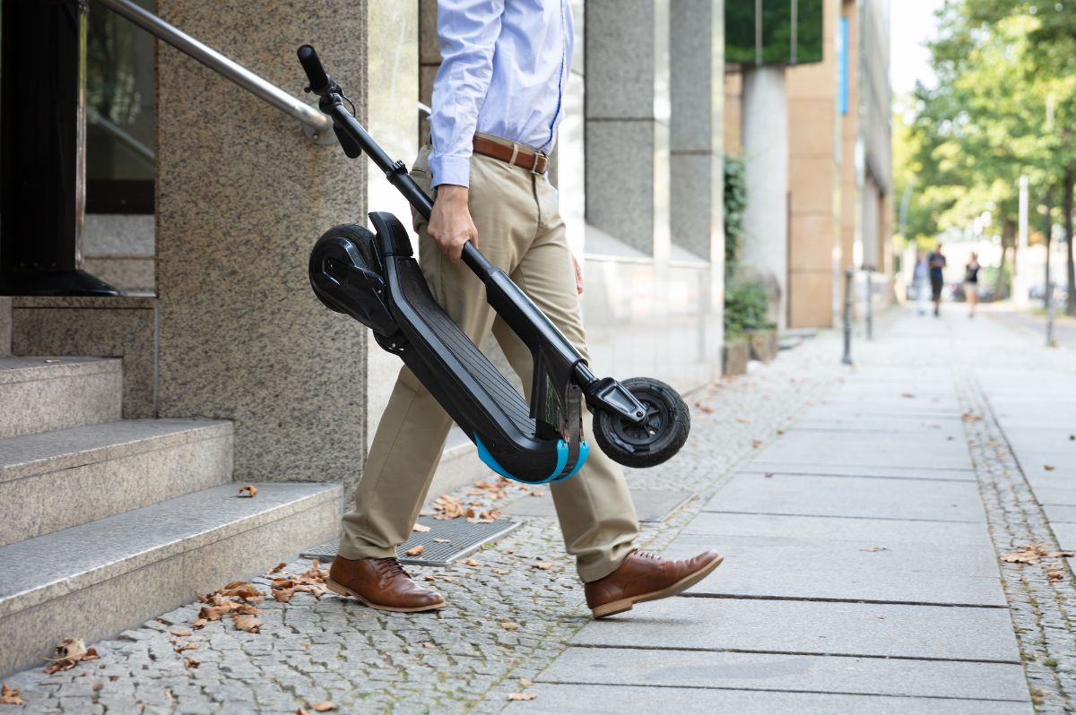 man holding folded scooter