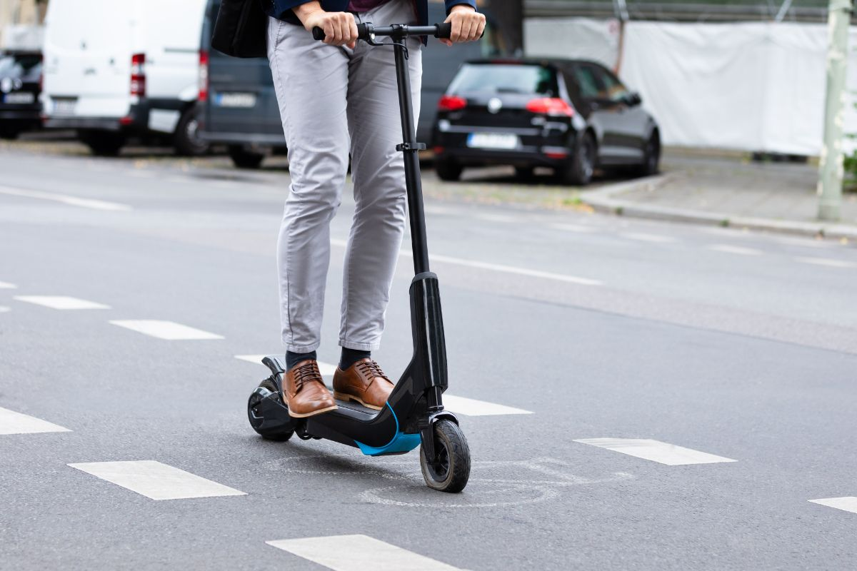 man riding via electric scooter on the road