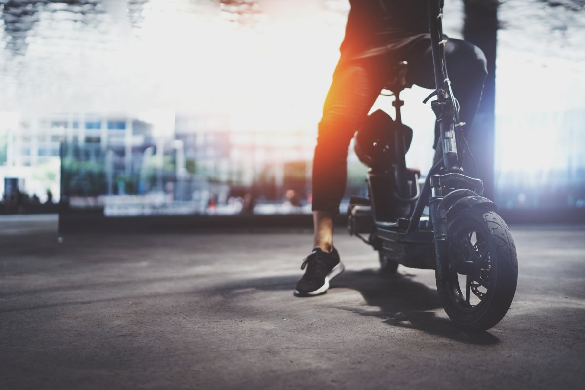 man sitting on his electric scooter