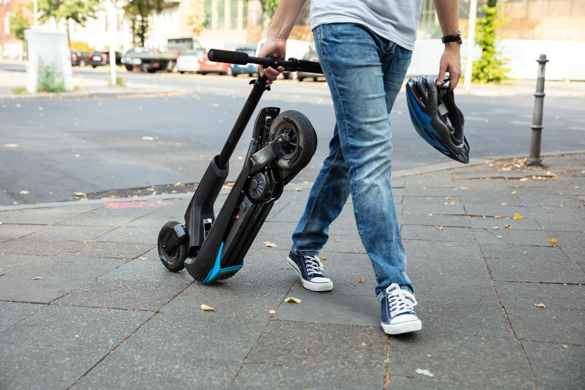 man with his folded electric scooter