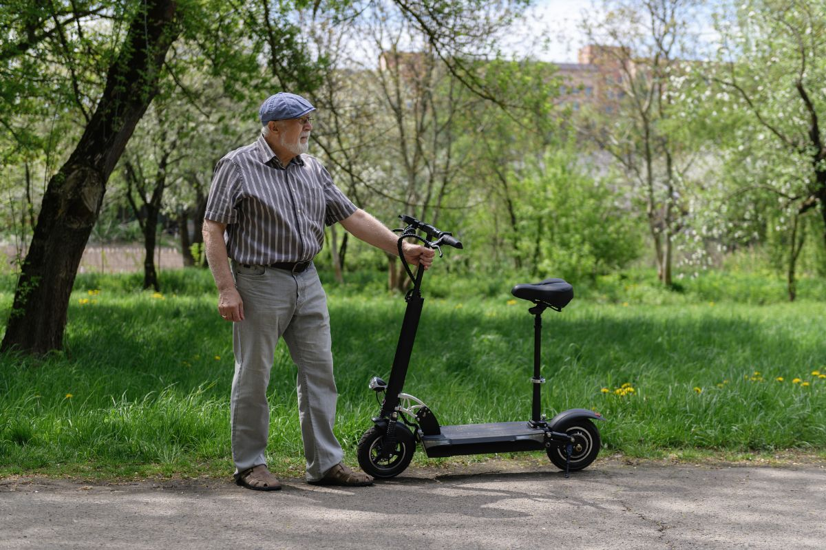 old man holding an electric scooter