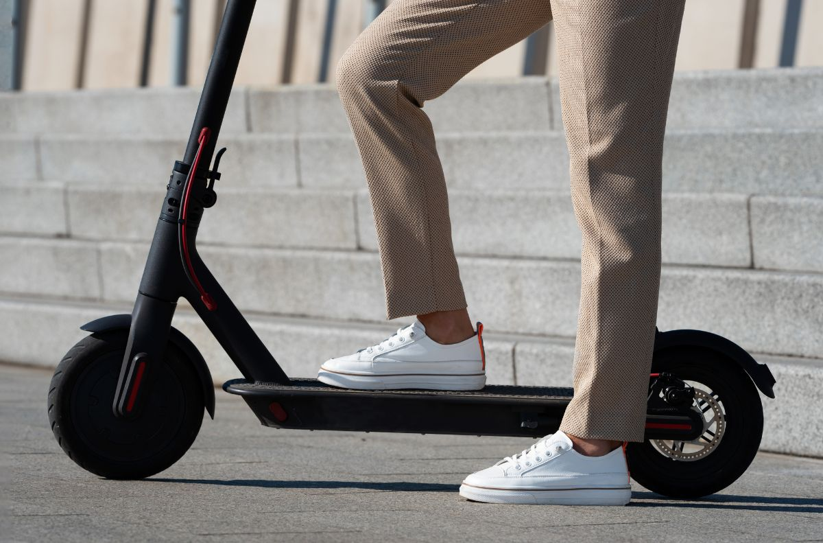 side view of electric scooter with man in a white shoes