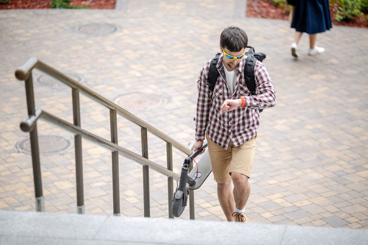 student carrying his folded electric scooter