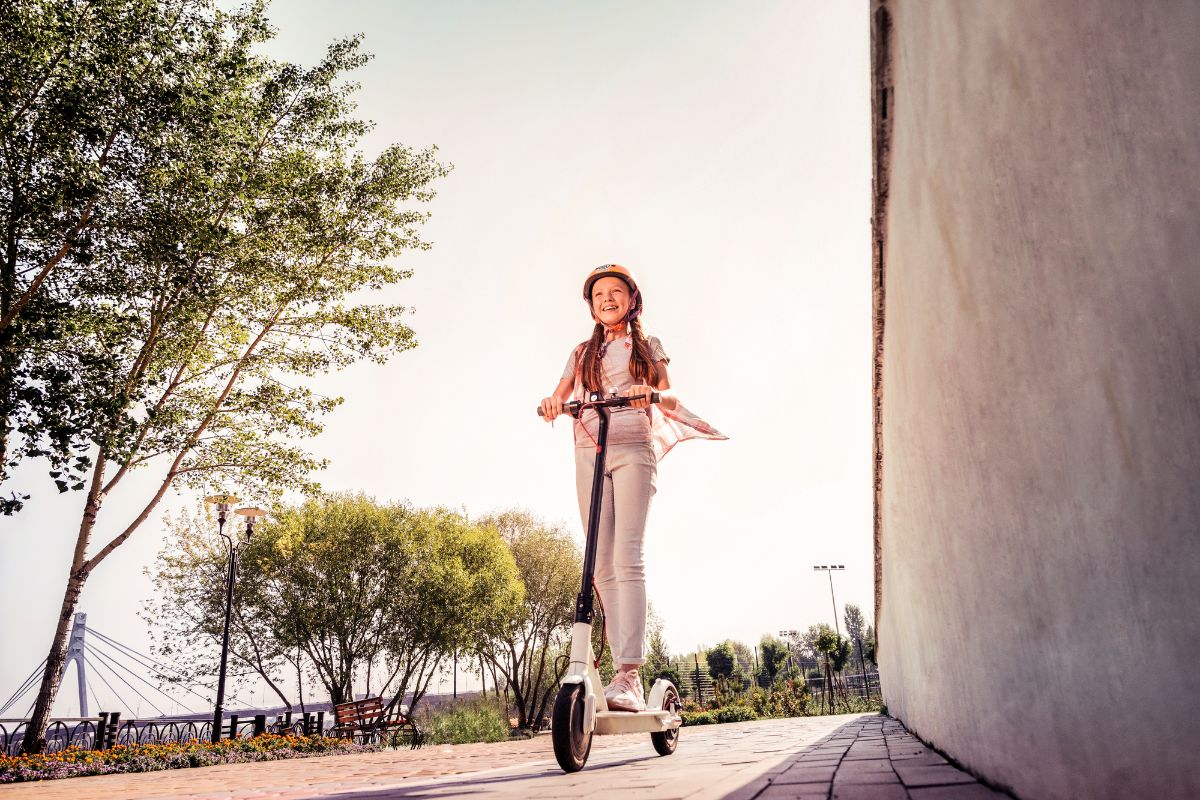 teenage girl riding electric scooter