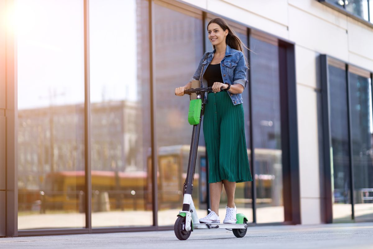 woman in green skirt riding electric scooter