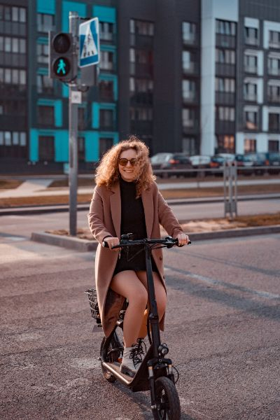 woman with brown coat riding electric scooter