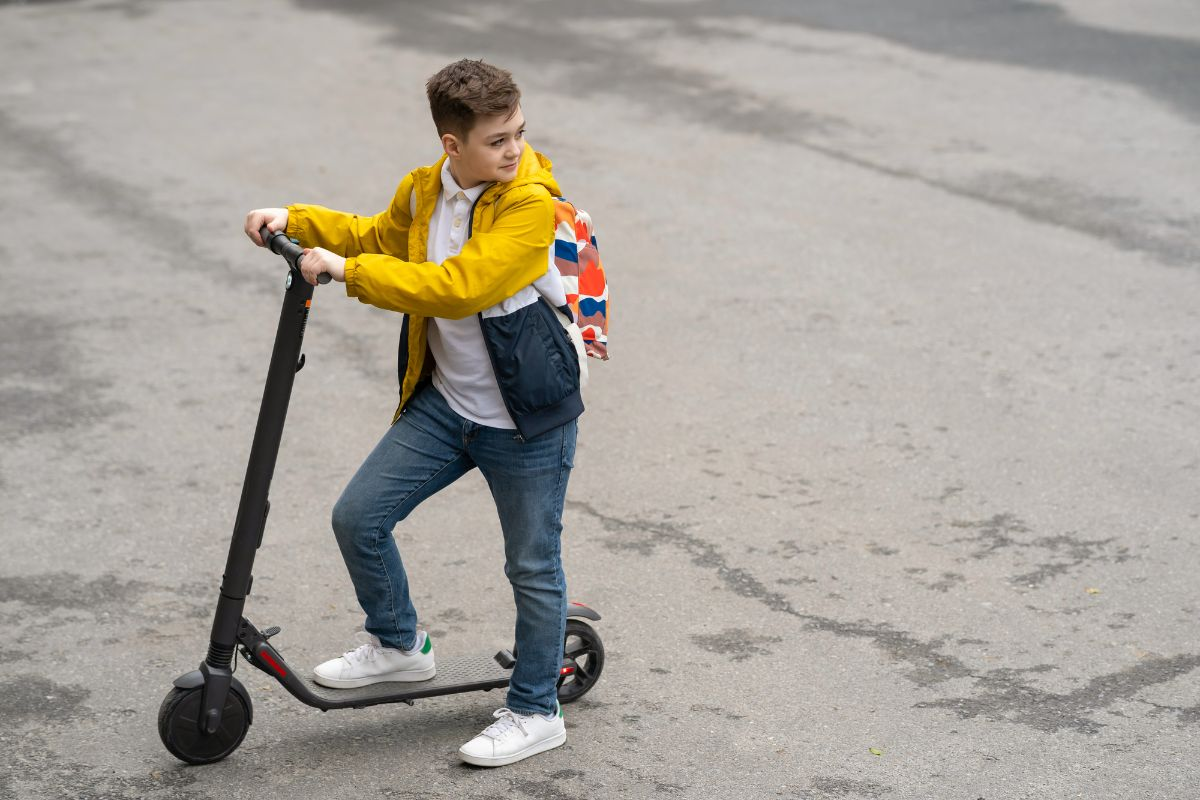 young boy riding electric scooter